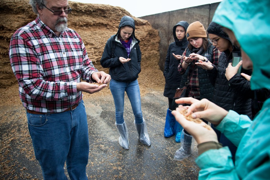 Dr. Erickson passes samples of corn silage around for students to feel and smell. Silage, a fermented, high-moisture stored fodder, is a primary ingredient in ruminant feed.Photo: Kathleen Nay